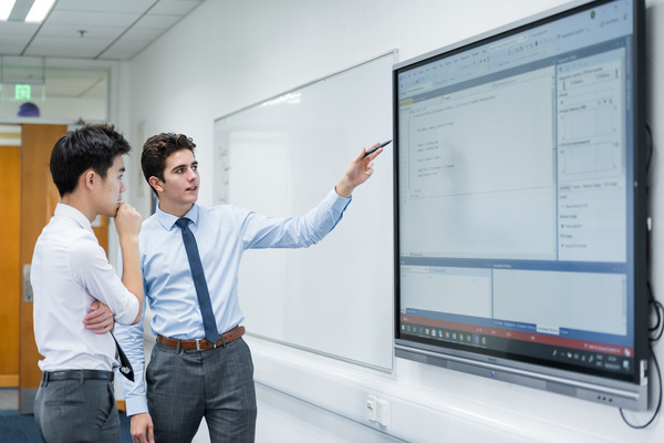 students talking in front of interactive whiteboard